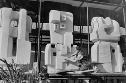 Henry Moore carving the figures for Time Life Screen 1952-53 Portland stone in front of his home, Hoglands.