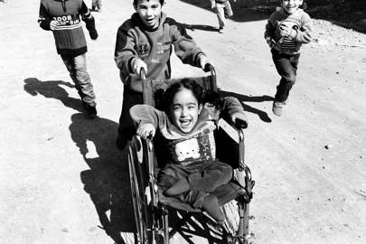 "Aya screams, ""Faster, donkey, faster!"" while being pushed in her wheelchair by her brother Mohamad – Tripoli, Lebanon. 2016"